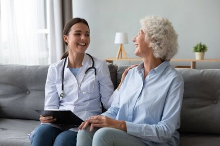 Friendly young nurse in white coat holding clipboard laughing with elderly female patient during homecare visit consultation, provide her support encourages aged woman enjoy warm talk seated on couch