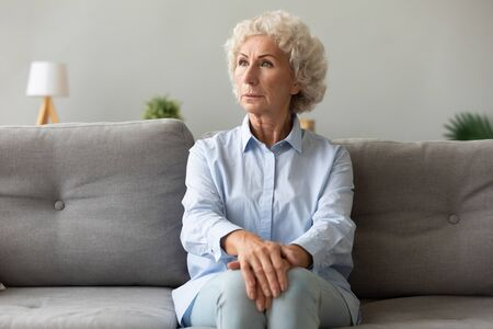 Pensive elderly woman sitting on couch looking away lost deep in her thoughts, she looks worried concerned or lonely, female has senile diseases symptoms memory loss, dementia, mental disorder concept Zdjęcie Seryjne