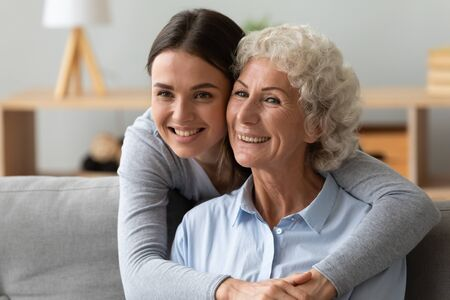 Close up adult granddaughter hugs from behind old relative grandmother showing her sincere relation strong connection, reverent attitude, deep respect, multi-generational family photo shooting concept