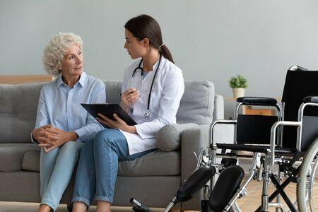 Doctor in white coat consults disabled patient explain diagnosis during homecare visit, nurse hold clipboard listen old woman fill medical form writes complaints, health care medical insurance concept Stock fotó - 149361917