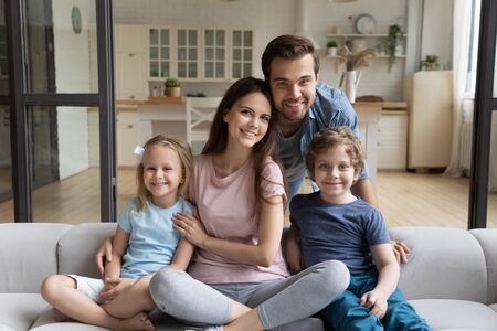 Portrait of happy young family with preschooler children sit relax on couch in home studio posing, smiling mother and father rest cuddle with little daughter and son, enjoy weekend together