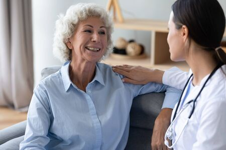 Aged woman talks with young caregiver seated on couch at home, female nurse in white coat puts hand on patient shoulder showing care support and friendly warm relation at visit homecare of old person