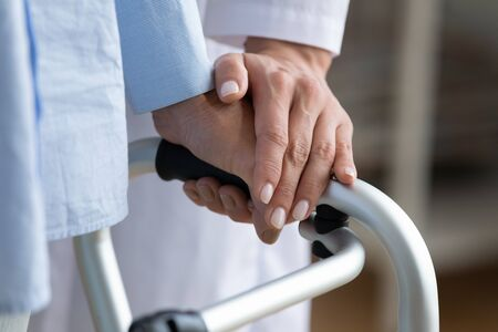 Physiotherapist touches disabled elderly woman hand while she holding walking frame close up view. Nurse supporting patient during exercise rehabilitation therapy. Caregiving, help, eldercare concept