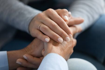 Close up adult daughter holding mothers hand, gesture symbol of psychological support in difficult period of life, fatal cancer disease, capacity understand feelings sharing of pain, empathy concept