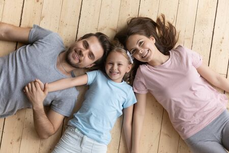 Top view portrait of loving young parents and little preschooler daughter lying on wooden floor relaxing together at home, happy family with small girl child hold hands show unity and support