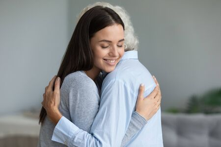 Millennial grown up granddaughter cuddles to elderly grandmother congratulate her with holiday, relatives women enjoy tender moment express sincere candid emotions showing love deep connection concept Stock Photo