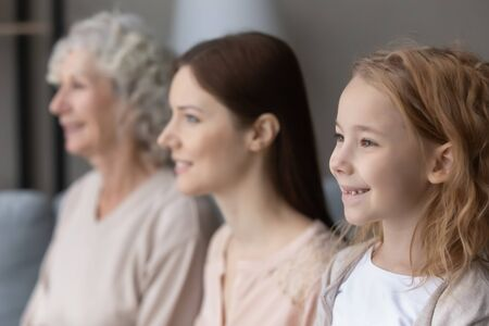 Profile view of happy three generations of women look in distance dreaming visualizing together, hopeful smiling little girl forefront with mom and mature grandmother imagine bright family future