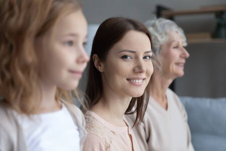 Close up profile view of three generations of women look in distance dreaming or visualizing, smiling young Caucasian mother look at camera, girl with mom and grandmother show family unity and bonding