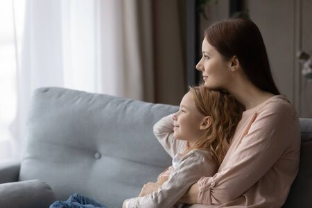 Young Caucasian mother and small preschooler daughter relax on sofa at home look in distance dreaming together, dreamy mom and little girl child hug cuddle, dream or visualize on couch in living room Foto de archivo