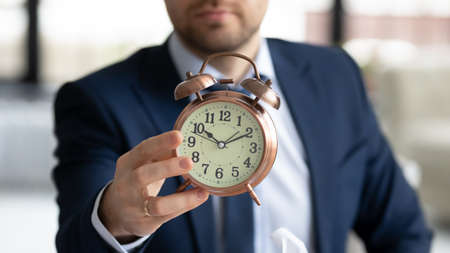 Crop close up of businessman hold show clock notify about deadline or time frame for new company project launch, male employer specify task startup limit, note about business meeting appointment