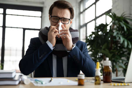 Unhealthy sick male employee sit at office desk blow runny nose suffer from cold or fever, ill man worker struggle with cold at workplace, take medications to relive symptoms, healthcare concept Stock Photo