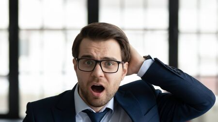 Close up portrait of frustrated young caucasian businessman in glasses stunned by unexpected notice or message, disappointed male employee or worker feel lost concerned or confused at workplace
