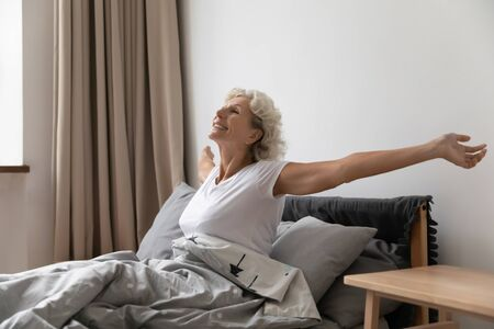Optimistic senior woman wake up from good healthy sleep in comfortable home bed, active happy mature female stretching exercising in bedroom in morning, awaken from dream, welcome new day smiling