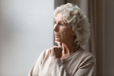 Pensive mature 50s woman look in window distance feeling sad melancholic at home, thoughtful anxious senior female lost in thoughts, thinking or pondering, elderly solitude, loneliness concept