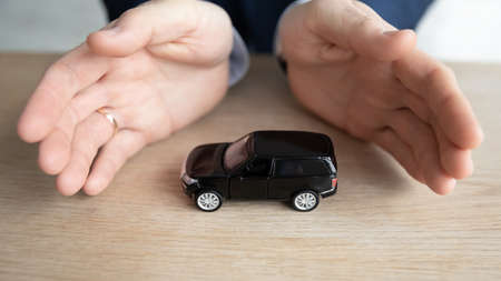 Crop close up male employee look at play with toy car at office table, businessman motivated for result, visualize plan buying new automobile, strive for business success, visualization concept Stok Fotoğraf
