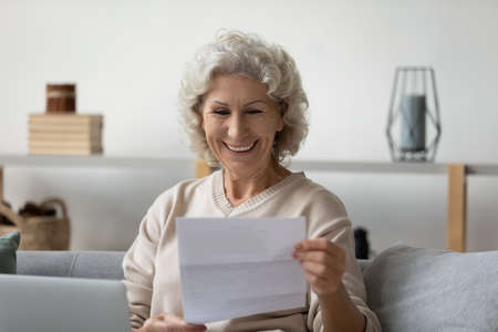Smiling elderly 60s woman sit on couch in living room feel overjoyed reading good news in postal paper letter, happy senior 50s female get pleasant paperwork bank notice or post correspondence