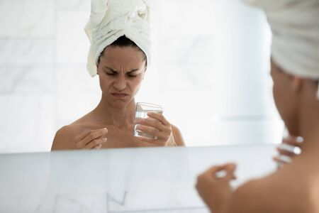 Mirror reflection close up unhealthy woman holding pill and glass of water, unhappy girl feeling unwell, taking painkiller, antidepressant or antibiotic medicine in morning, headache or depression 스톡 콘텐츠