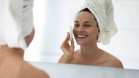 Close up head shot smiling woman cleaning skin with facial cleansing sponge, attractive girl wearing white towel on head looking in mirror, enjoying face care procedure, removing makeup Фото со стока