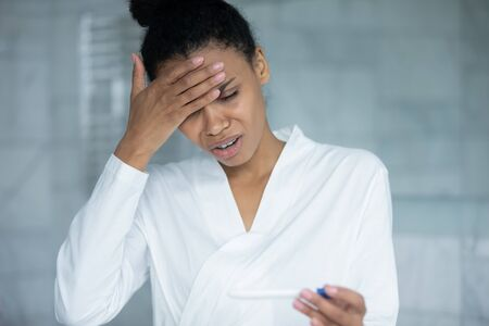 Close up unhappy stressed African  woman wearing bathrobe holding pregnancy test, girl dissatisfied by result, standing in bathroom, unwanted pregnancy or health problem, infertility