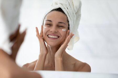 Head shot mirror reflection smiling woman with towel on head applying moisturizing face cream under eyes, touching enjoying perfect smooth skin, doing facial massage in bathroom, skincare procedure Standard-Bild