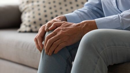 Elderly woman seated on couch touches knee suffers from repeated painful feelings on knee pain related to aging process close up image, tendonitis and arthritis diseases, joint degeneration concept Stock fotó