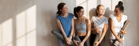 Multi racial girls wear active wear talking standing near wall holding personal mats wait for yoga session, wellness, weight loss, body care concept. Horizontal photo banner for website header design