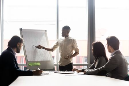 African skilled employee makes presentation on flip chart share thoughts to diverse teammates during morning briefing in board room. Young startupper presents for investors new fresh cool idea concept Stock fotó