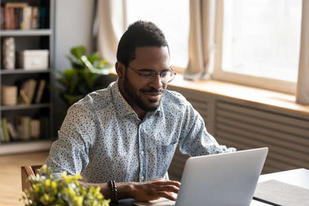 African millennial guy sit at desk at home or cozy modern office room look at laptop screen do remote job, contacting distantly with friend or clients, makes order use online services delivery concept