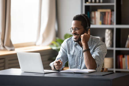 African guy student learn on-line use headphones with mic and pc holds pen takes notes in notebook sit at desk at home. Businessman wear headset talk by conference call do video chat working at office