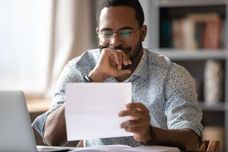 African man sit at desk hold postal correspondence letter read good news feel proud by personal business achievement, got hired, receive reward, financial success statement, approved bank loan concept
