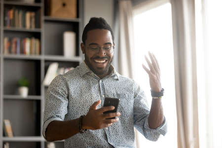 African man in casual clothes holds smartphone read message feels excited. Fast internet 5g connection, got sms favorite web shop virtual services promotion special offer great discounts sales concept