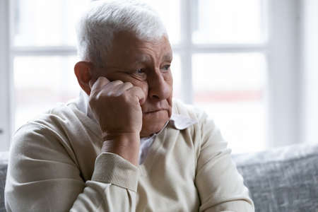 Close up head shot sad lonely mature man lost in thoughts, sitting on couch at home, touching cheek, thoughtful depressed older elderly male thinking about past, looking away, loneliness concept Stockfoto