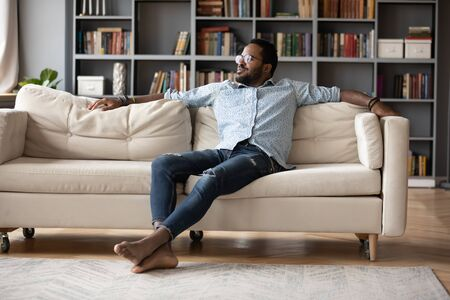 Carefree relaxed african man resting sit on sofa in cozy living room looking out the window enjoy lazy free day. Warm home owner, modern rented apartments, breath fresh conditioned air indoor concept