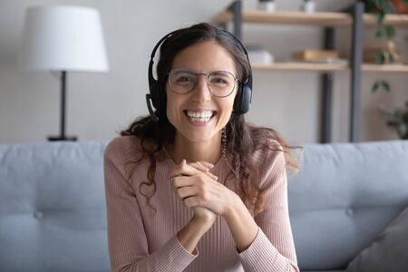 Head shot portrait smiling woman wearing headset with microphone and glasses looking at camera, overjoyed excited girl wearing headphones posing for photo, making video call, recording webinar Archivio Fotografico