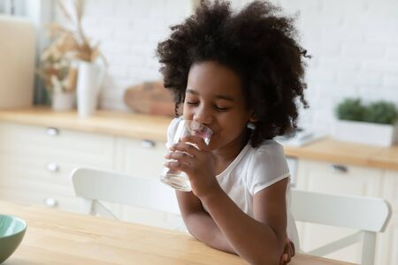 Close up image little mixed-race girl sitting at table in kitchen holding glass enjoy still or mineral water reduces thirst drinks clear aqua, healthy beverage, natural hydration body balance concept Stock fotó