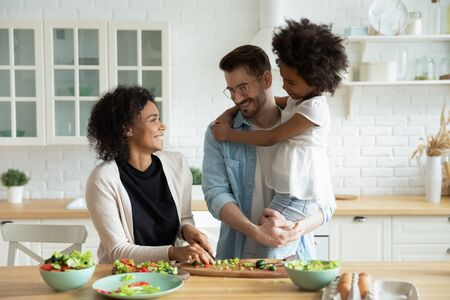 Caucasian dad holds on hands little mixed-race daughter while African wife preparing healthy vegetable salad family enjoy conversation in kitchen. Healthy home food, communication and cookery concept