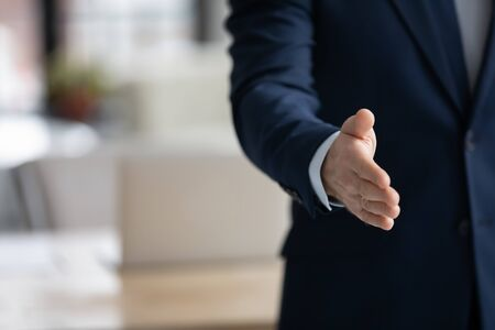 Crop close up of Caucasian businessman stretch hand acquainted with partner or client in office, male boss or employer greeting ready to shake hand of newcomer at workplace, employment concept Stockfoto