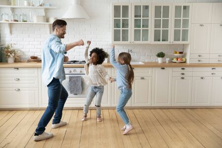 Caucasian father multi-racial school age daughters enjoy dance battle funny activity in modern new renovated kitchen spend active time together on weekend at home. Have fun, happy fatherhood concept Banque d'images