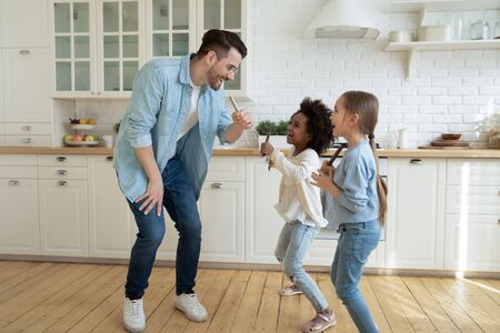 Daddy with multi-ethnic small African Caucasian daughters spend free time together having fun dancing holding forks and hand beater like microphones sing in kitchen listen music enjoy weekend at home