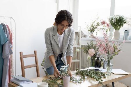 Young Caucasian female interior designer compose flowers in handmade decorations on desk at home, millennial woman florist or gardener make floral house decor compositions for sale, gardening concept