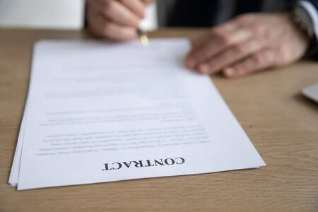 Crop close up of businessman put signature on paper document make agreement in office, male boss or CEO sign paperwork contract close deal with business partner or client, partnership concept