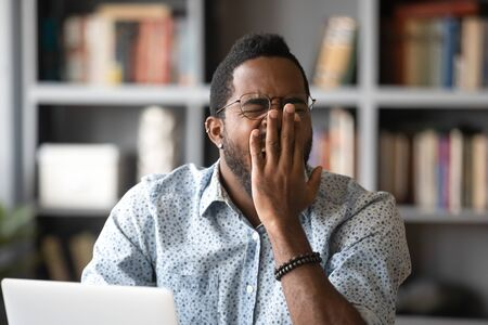 African 30s man sitting at desk in front of laptop, yawns covers mouth with palm feels unmotivated at workplace. Concept of drowsiness, overworked freelancer, boring job, early morning Monday concept