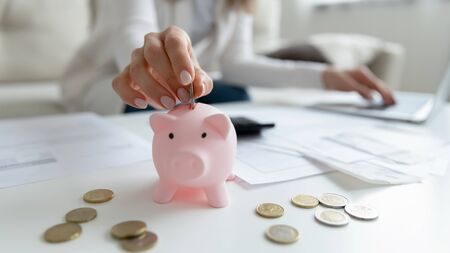 Close up coffee table lot of invoice, financial stats documents, utility bills, household payments, focus on female hand puts coin in piggy bank. Family budget manage, making personal savings concept Stok Fotoğraf