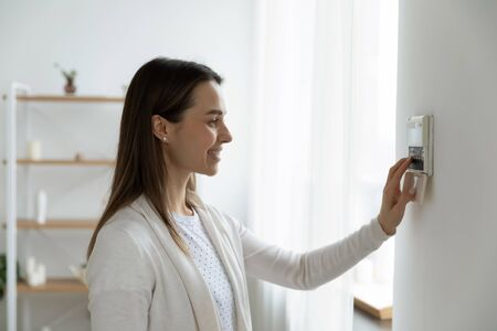 Smiling woman standing near wall-mounted device adjusting degrees in living room set comfortable temperature using thermostat home heating system. Owner of modern smart house, energy saving concept