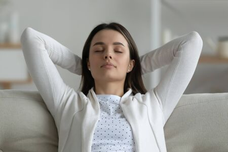 Peaceful young woman closed her eyes enjoy fresh air relaxing reducing fatigue, daydreaming leaned on sofa in cozy living room put hands behind head feels inner harmony, mindfulness. No stress concept