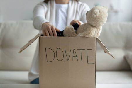 Woman sitting on couch at home put used clothes, soft toy in cardboard donation box close up image. Girl involved in aid nonprofit organization, selfless act of giving, generosity and charity concept