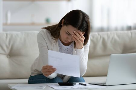 Stressed woman sit on sofa read bad news notification paper letter from bank about debt or eviction, calculate domestic bills has financial problems feels worried, lack of finances, bankruptcy concept Archivio Fotografico