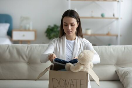Young woman sitting on couch preparing parcel for sending to needy human. Girl with big kind heart puts used clothes new wear and soft bear toy in donation box, concept of caring about homeless people Stok Fotoğraf