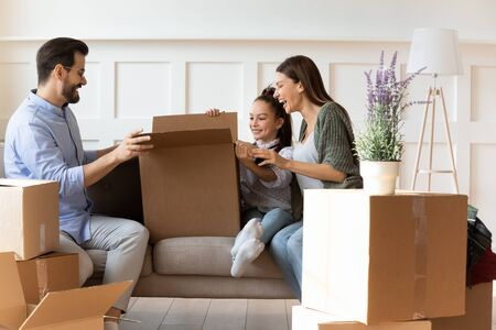 Adorable daughter helping parents with cardboard boxes on moving day, happy family with child sitting on couch, unpacking belongings in modern living room, relocation and mortgage concept Stockfoto