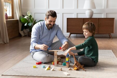 Happy father playing with little son, sitting on warm floor with underfloor heating, smiling dad and cute boy having fun, building tower from colorful wooden blocks, enjoying leisure time together